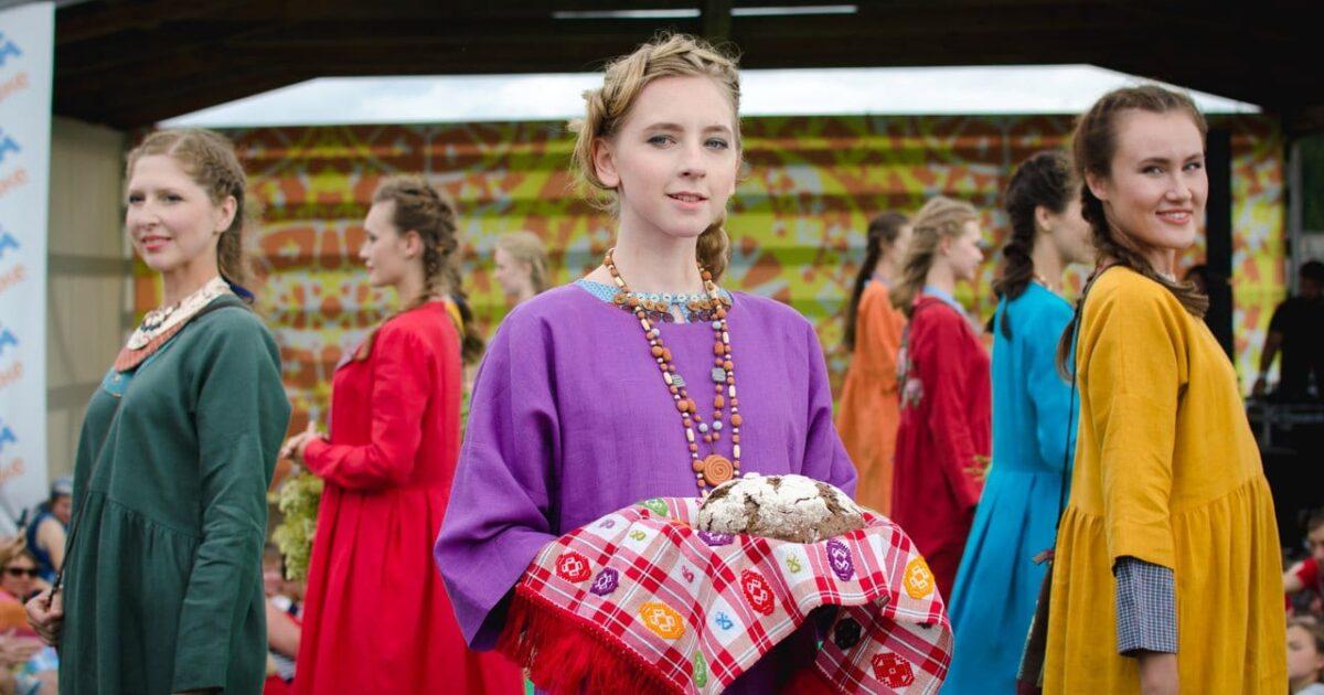 Девушка с плетеной косой держит хлеб на рушнике