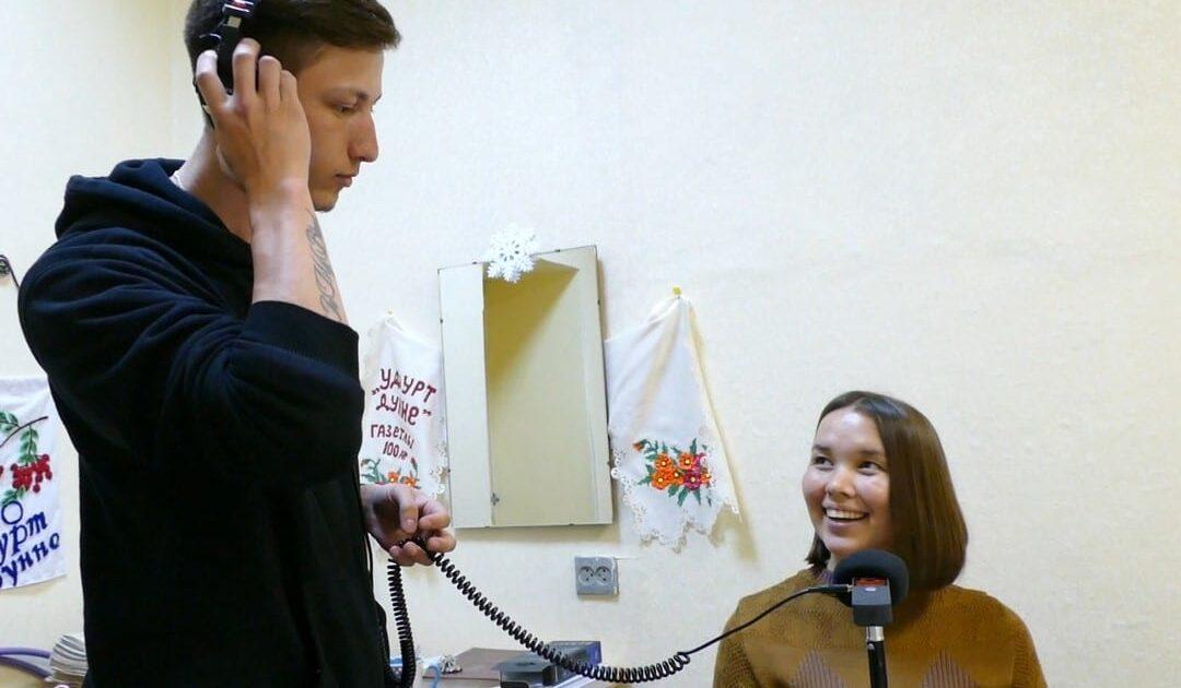 Молодой человек в наушниках слушает девушку через рекордер zoom h1