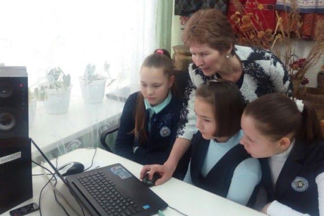 Фото женщина показывает девочкам презентацию на компьютере на удмуртском языке