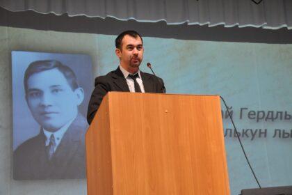 Фото Александра Егорова за трибуной, на фоне проекции Кузебая Герда