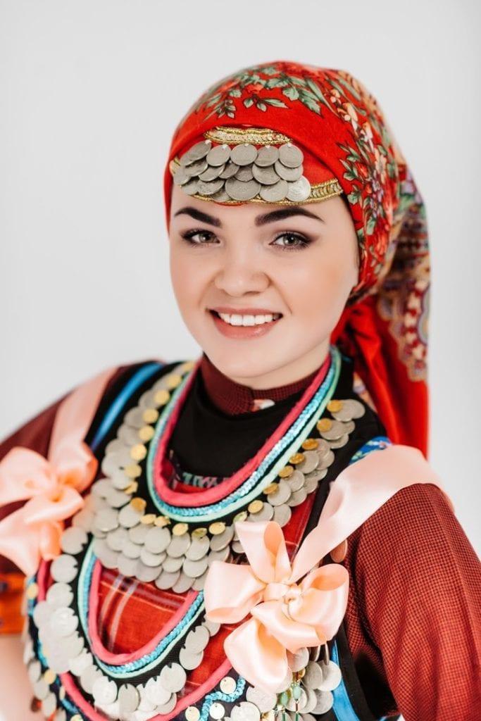 Фото счастливая девушка с монисто, в платке, с бантами на груди