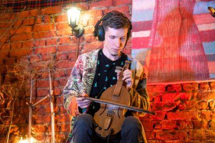 Фото Чудья Жени, который играет на кубызе в наушниках на фестивале Кубыз-фест