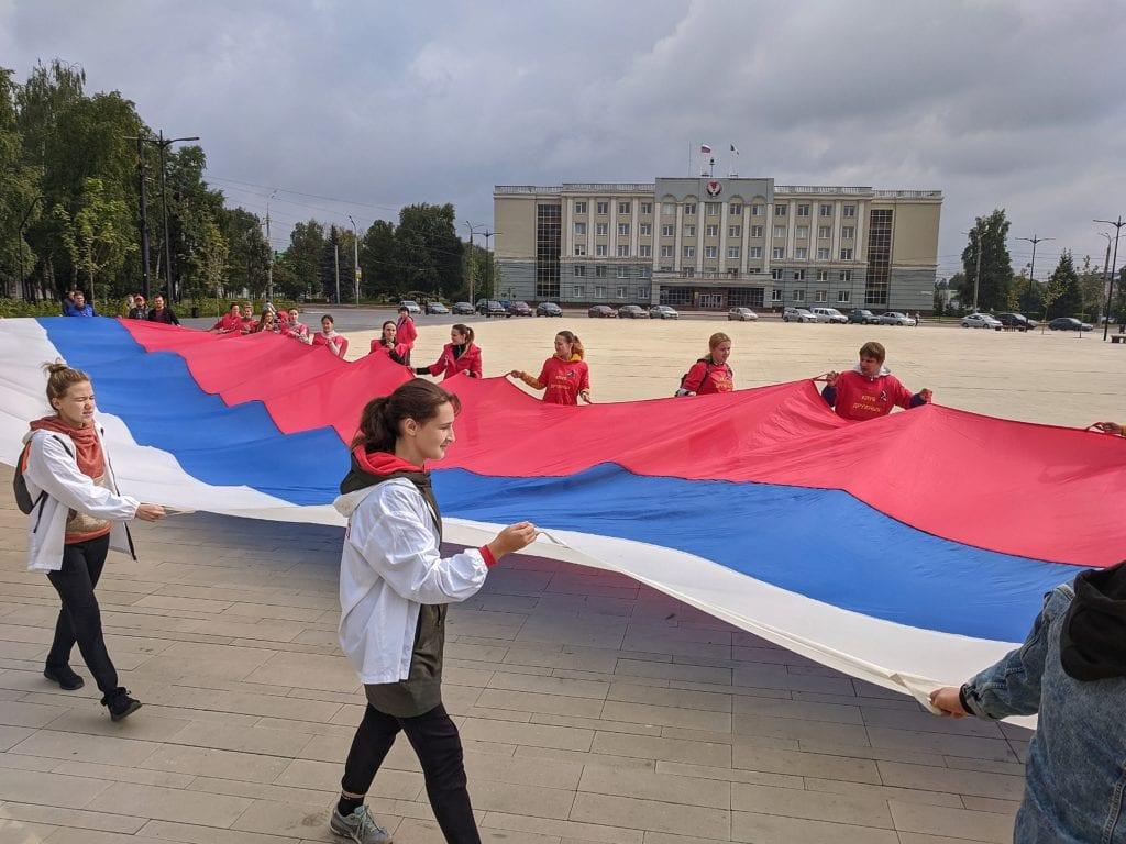 Фото волонтёры несут огромный флаг России перед зданием правительства в Ижевске