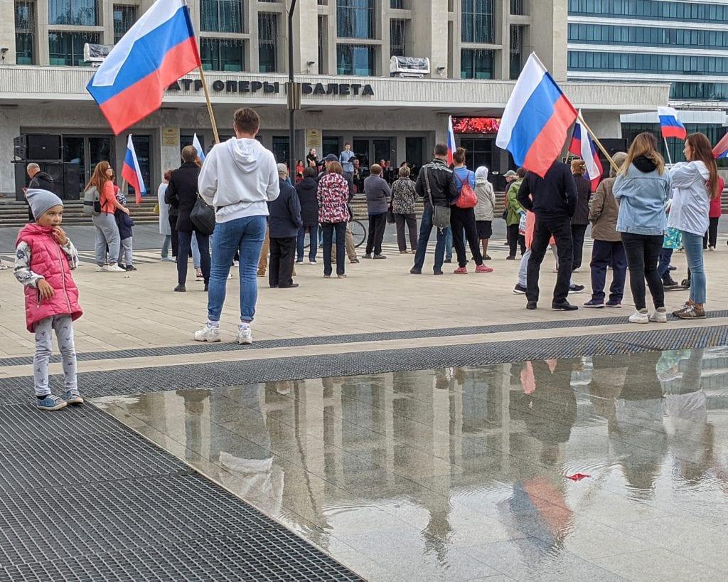 Фото девочка рядом с музыкальным фонтаном на фоне флагов России