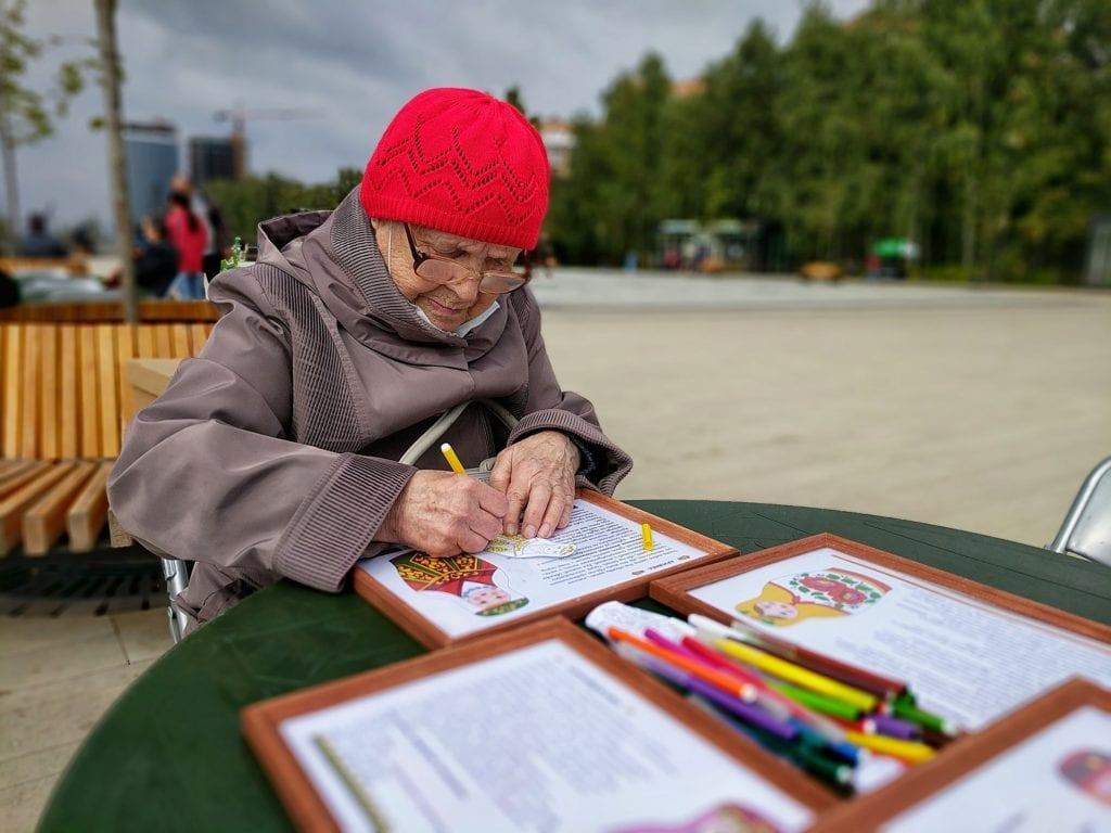 Фото бабушка в красной шапке раскрашивает матрёшек на мастер-классе Дома Дружбы народов