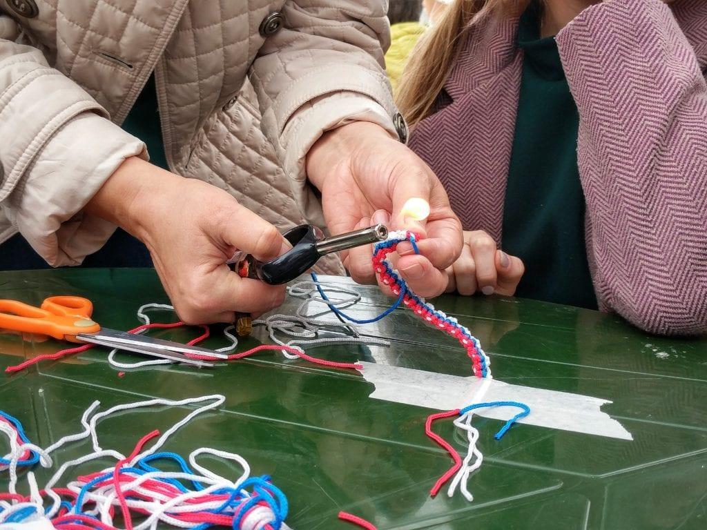 Фото мастер-класса по плетению браслетов цветов флага рф, обжигают зажигалкой концы веревочек