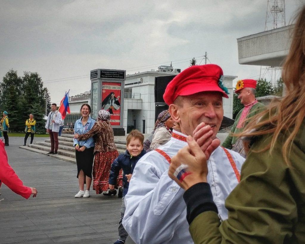 Фото мужчина в красной шапке танцует на дне флага РФ