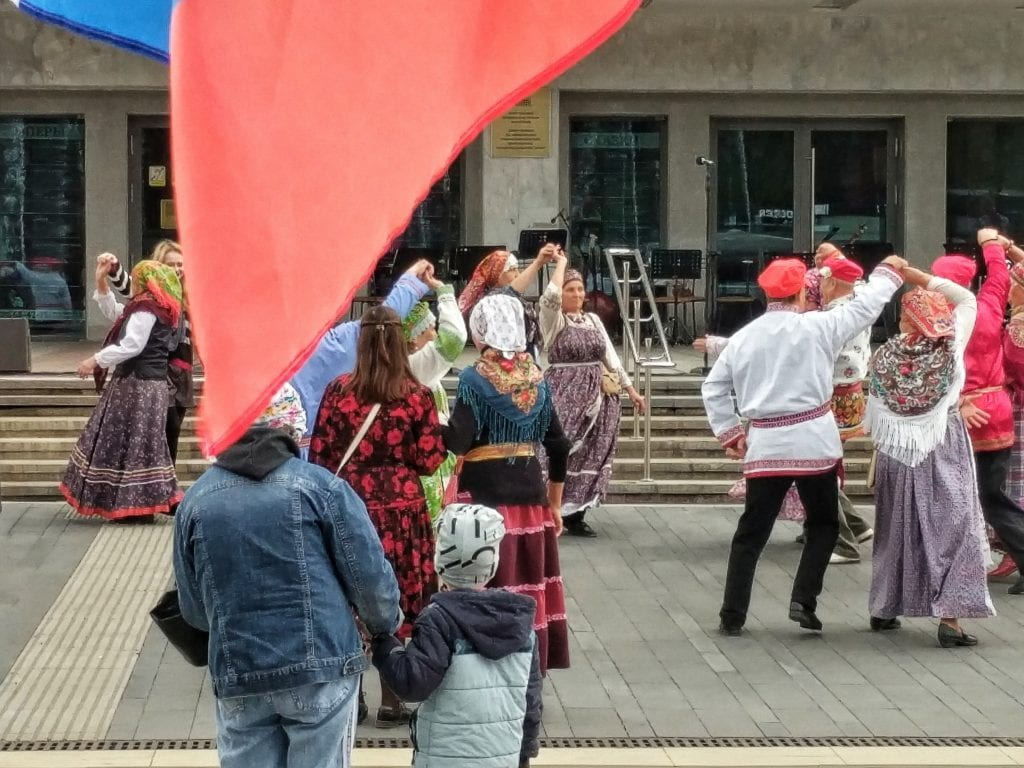 Фото люди танцуют на дне государственного флага России, флаг развевается на переднем плане