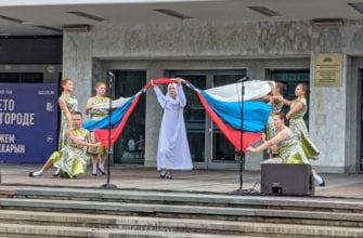 Фото выступление девушка в белом одеянии проходит под флагом России