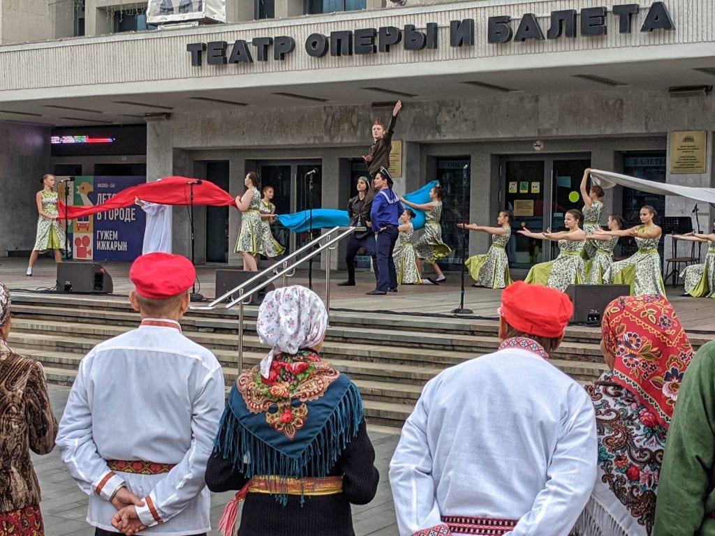 Фото зрители смотрят выступление артистов у театра оперы и балета на дне флага рф