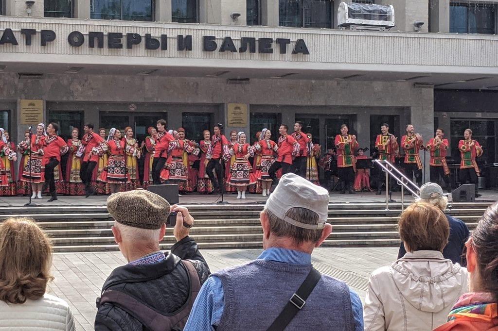 Фото зрители смотрят выступление артистов в национальных костюмах у театра оперы и балета