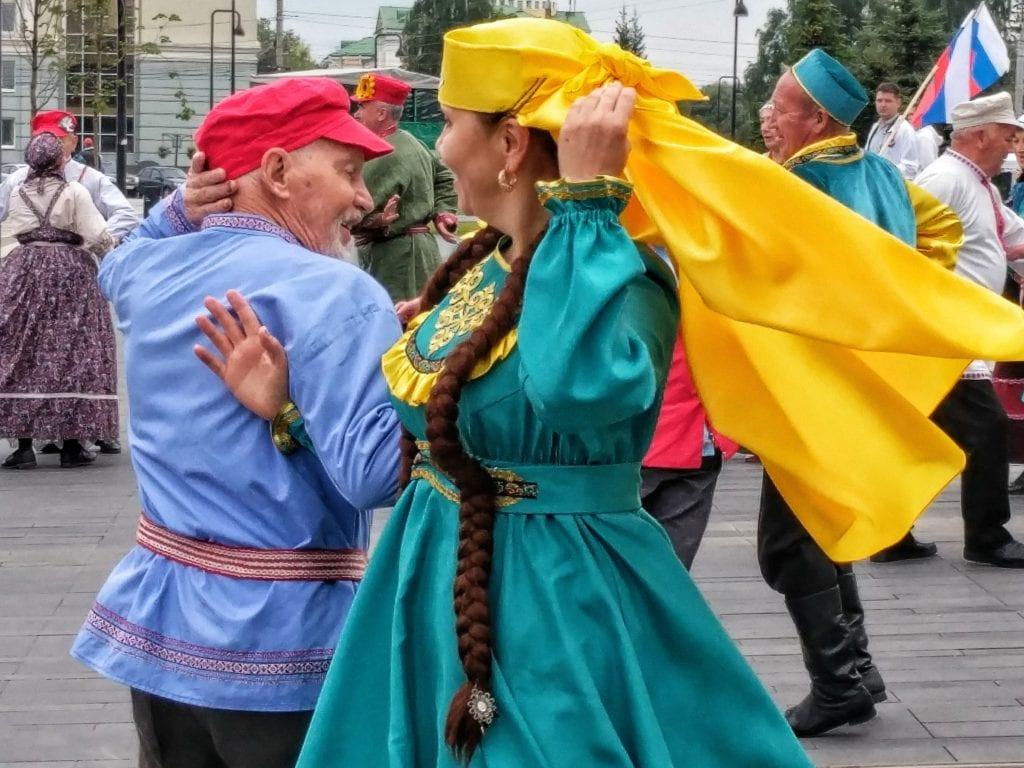 Фото мужчина в национальном русском костюме и женщина в национальном татарском костюме танцуют вместе