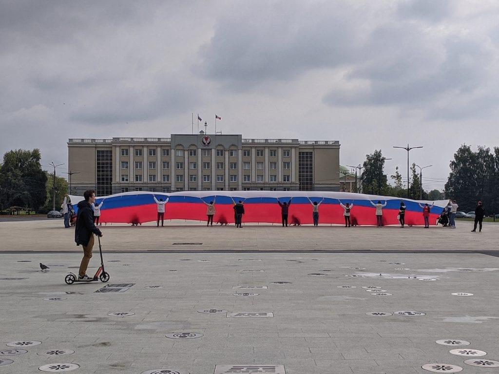 Фото огромного флага России перед зданием правительства, на переднем плане проезжает мужчина на самокате