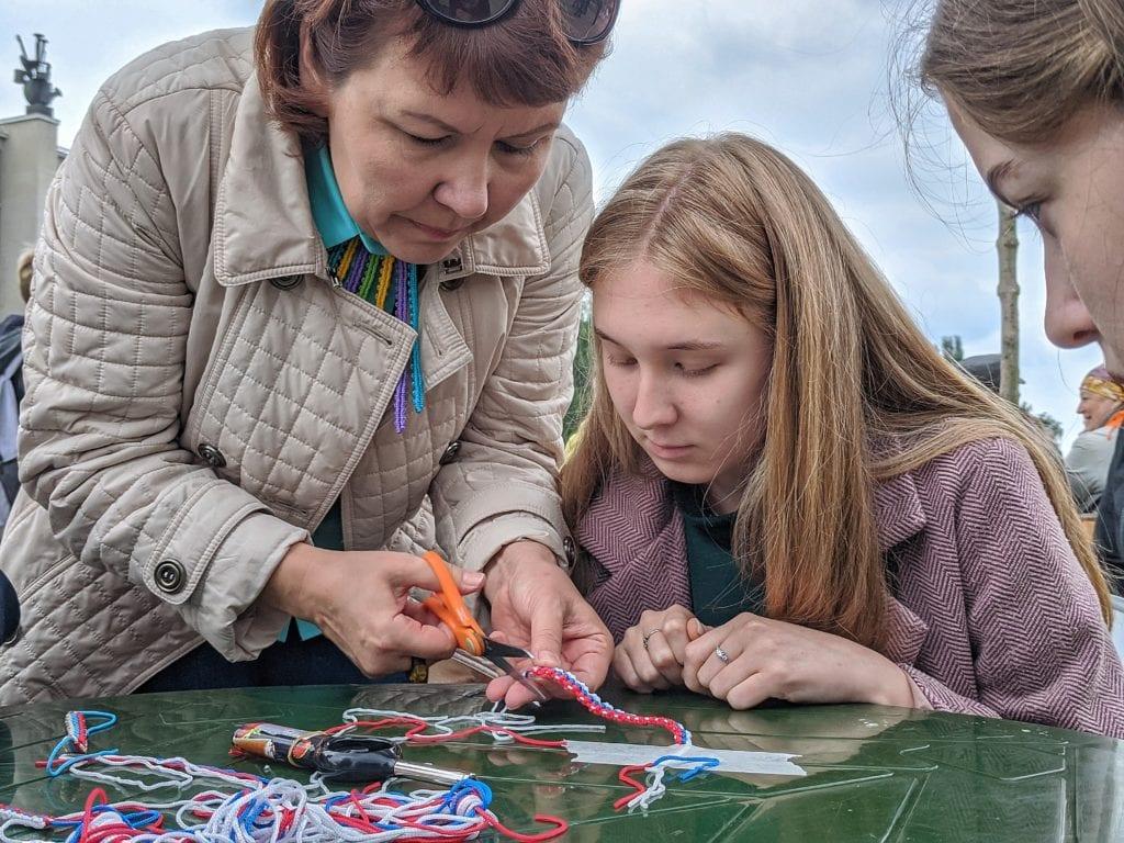 Фото наталья Шергина помогает девушке в изготовление браслета цвета флага России