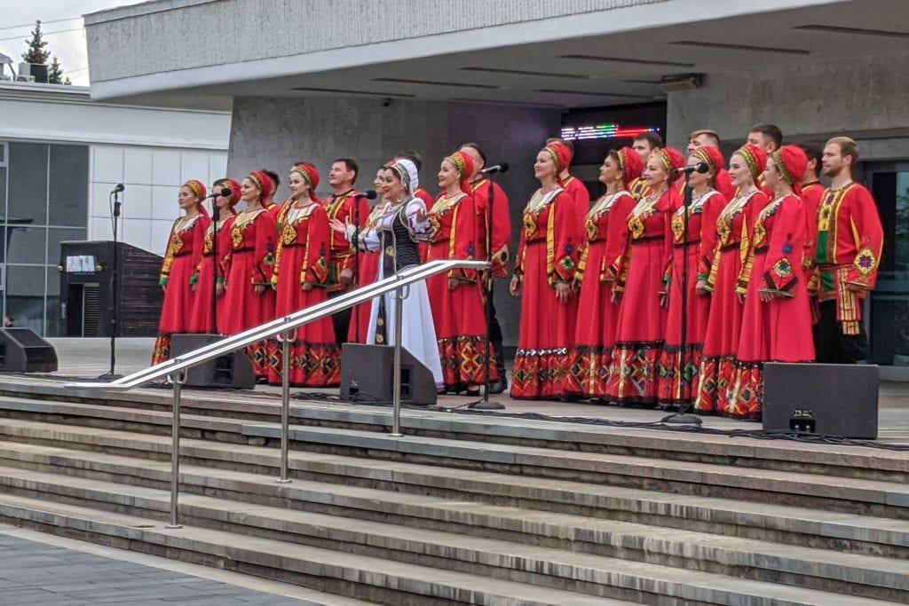 Фото женщины в красных одеждах выступают рядом с театром оперы и балета в Ижевске