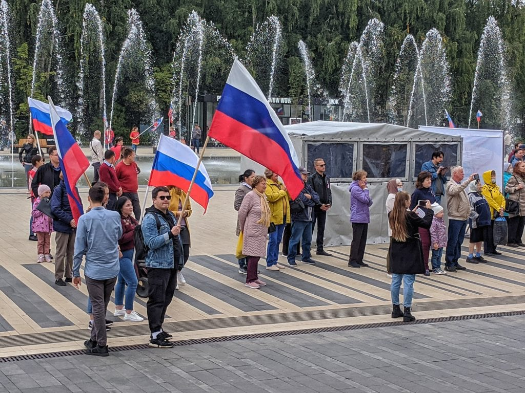 Фото люди на фоне фонтанов ходят с флагами России
