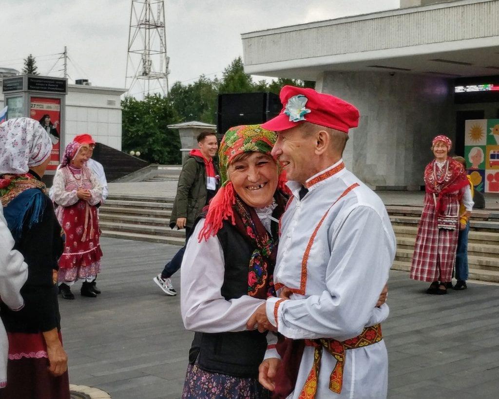 Фото мужчина и женщина в национальных русских костюмах улыбаются и смеются