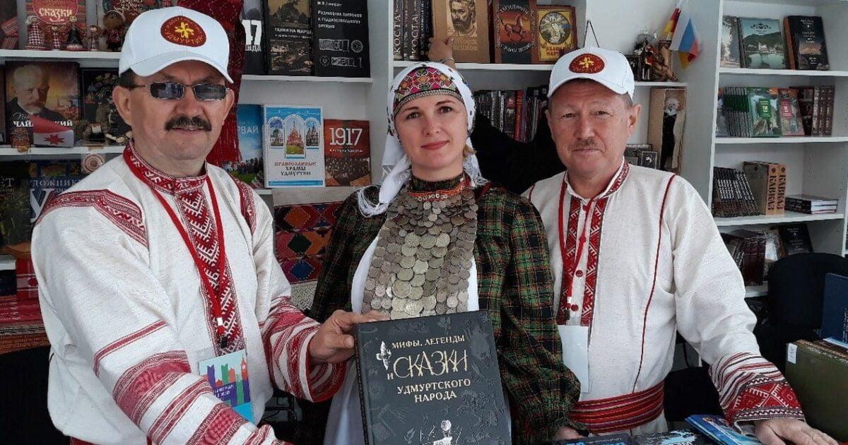 Фото издательство Удмуртия двое мужчин и женщина в национальных удмуртских костюмах держат книгу мифы, легенды и сказки удмуртского народа