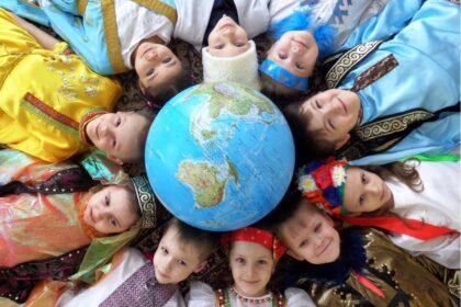 Фото дети в разных национальных костюмах лежат вокруг глобуса