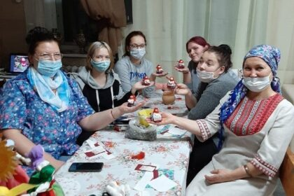 Фото женщины в масках сделали из глины голубей в фартуках