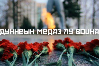 """Фото гвоздики на фоне Монумента боевой и трудовой славы, надпись """"дуннеын медаз лу война"""""""