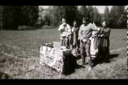 """ЧБ фото люди стоят в поле рядом со столом с надписью """"эктоника"""""""