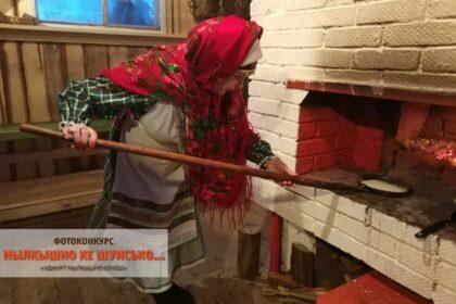 Фото женщина в фартуке с платком ставит ухватом в русскую печь табань