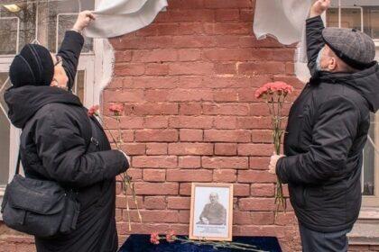 Фото мужчина и женщина с гвоздиками в руках снимают ткань с мемориала Иосифу Наговицыну