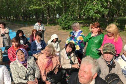 Фото люди в парке слушают выступления, Татьяна Ишматова стоит в зеленом пиджаке