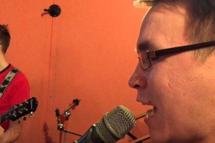 Фото Богдан Анфиногенов крупным планом у микрофона на оранжевом фоне