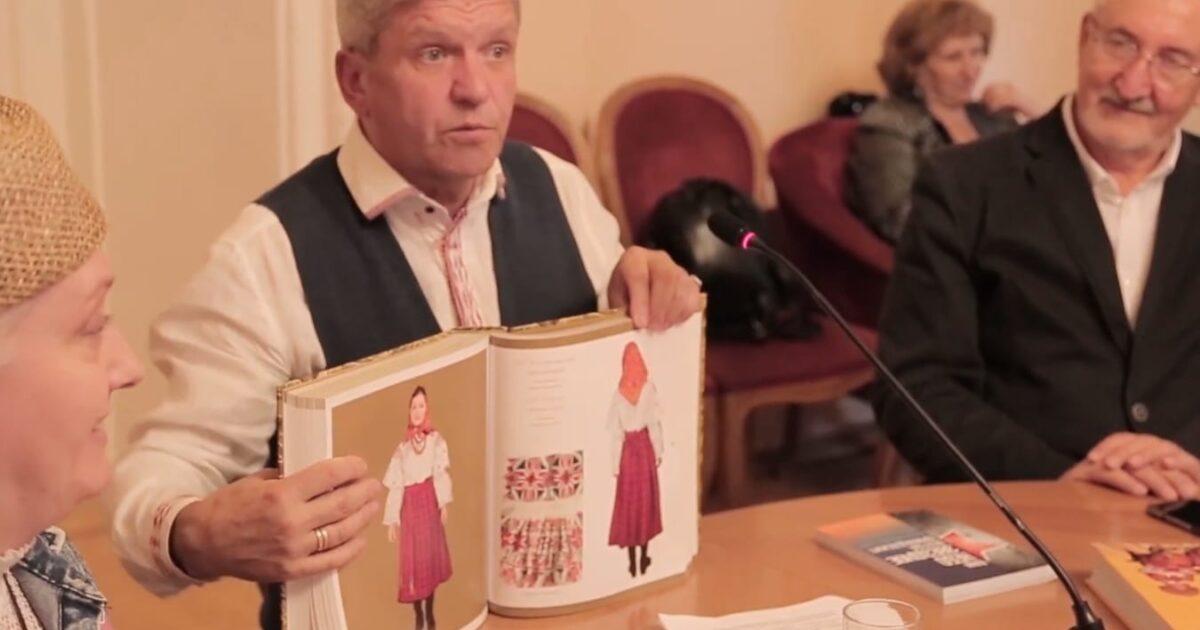 Фото коллекционер костюмов показывает книгу со своими костюмами