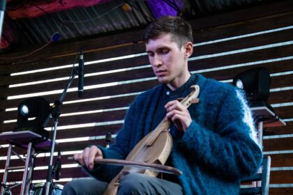 Фото Чудья Жени играет на кубызе в синем кардигане