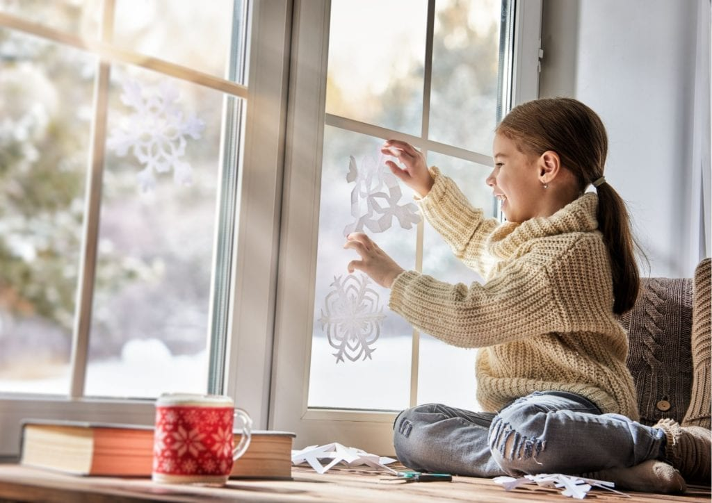 Фото девочка вешает вырезанную из бумаги снежинку на окно